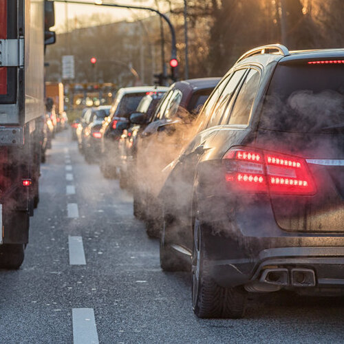 Busy road with several cars surrounded by car exhaust.