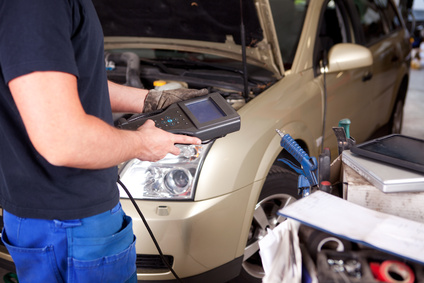 Detail of a mechanic with an electronic engine diagnostics tool